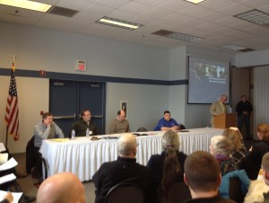Commission officials and the audience listen to the Enbridge representatives' presentation.